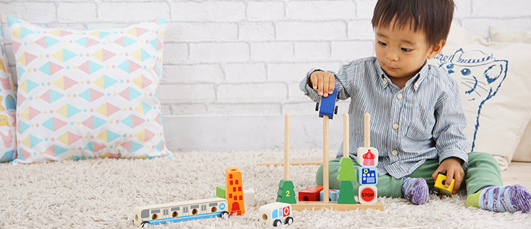男の子に人気のミニカーの木のおもちゃで遊ぶ1歳の男の子