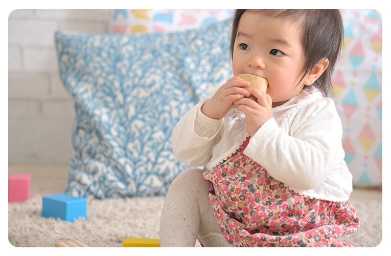 積み木を口にする赤ちゃん