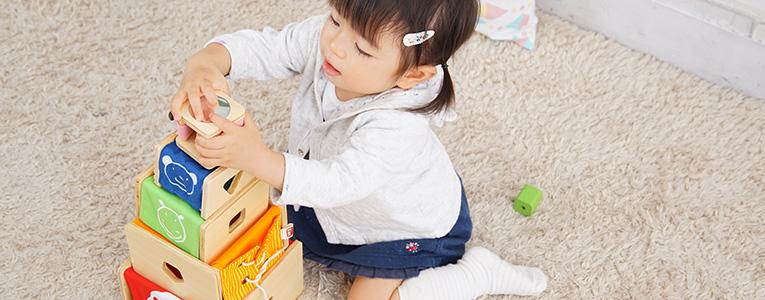 木のおもちゃで遊ぶ2歳の子ども