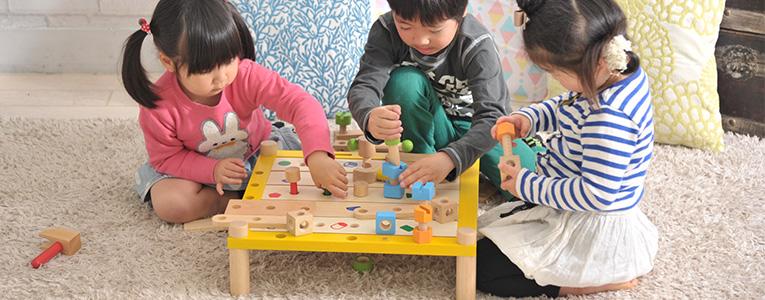 木のおもちゃで遊ぶ3歳の子ども